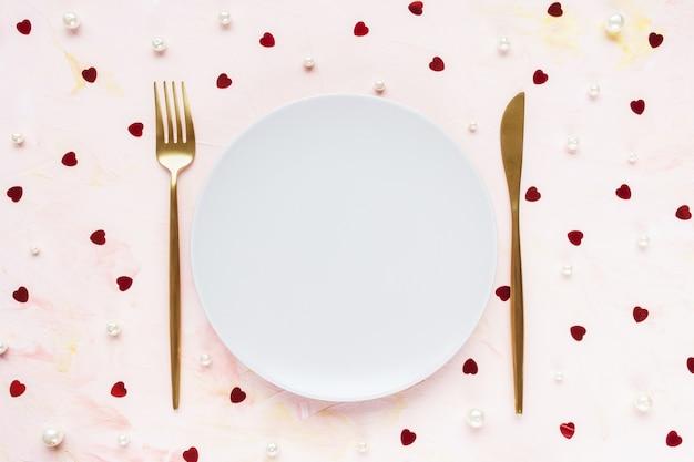 Posate d'oro e piatto in rosa con cuori. giorno di san valentino, pasto, cena e concetto di data