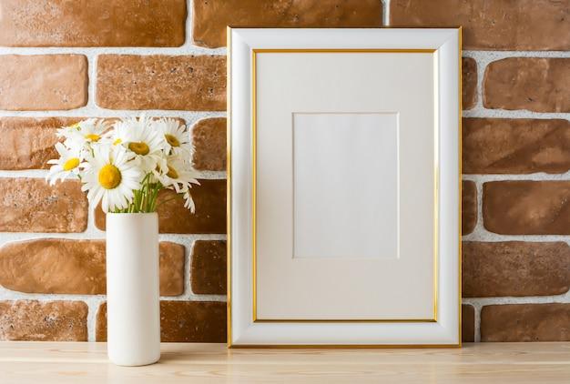Mockup cornice decorata oro con muro di mattoni a vista bouquet margherita