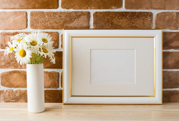 Mockup di cornice decorata in oro con bouquet di margherite in vaso
