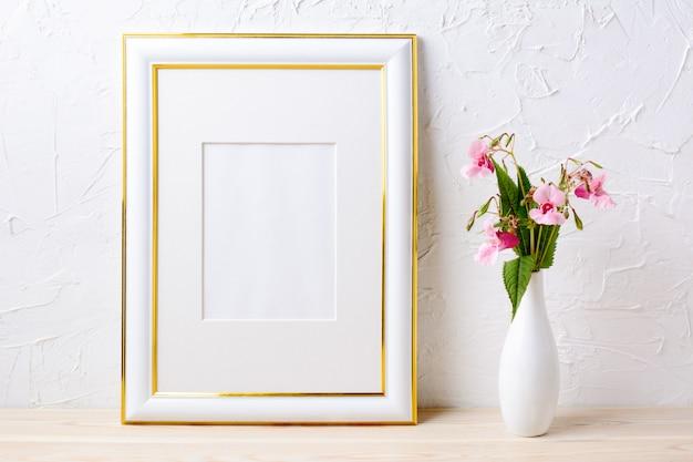Mockup cornice decorata in oro con bouquet di fiori in elegante vaso