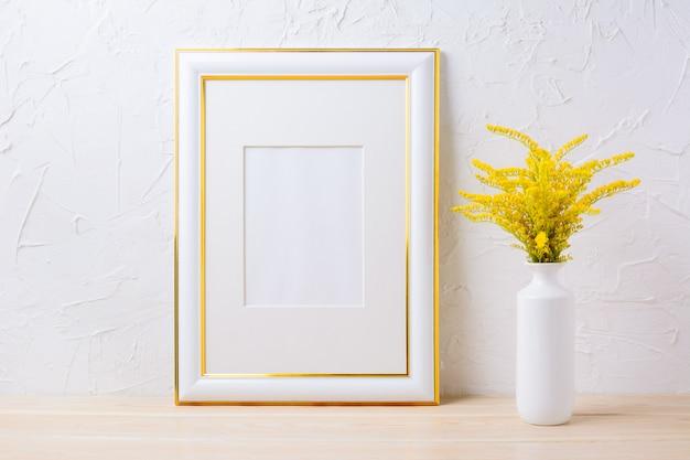 Mockup di cornice decorata oro con erba di fioritura gialla ornamentale in vaso