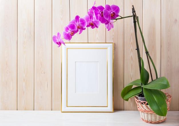 Mockup di cornice decorata oro con orchidea viola nel cestino di vimini