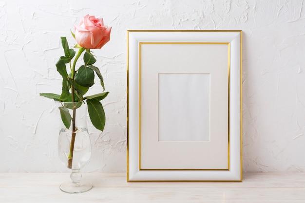 Mockup di cornice decorata in oro con rosa in squisito vaso di vetro