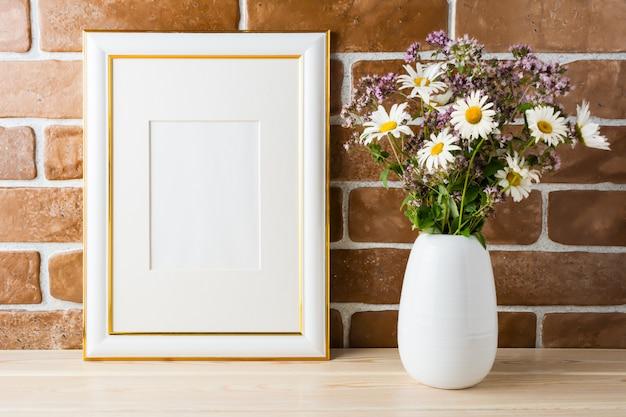 Mockup cornice decorata oro con muro di mattoni a vista bouquet di fiori di campo