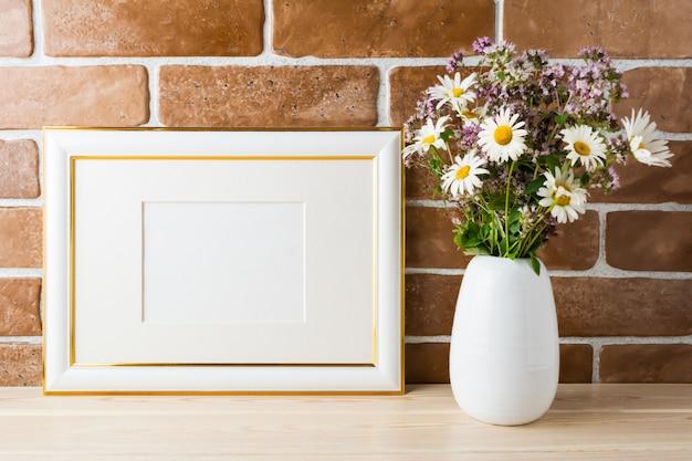 Mockup di cornice decorata in oro con bouquet di fiori di campo in vaso in stile