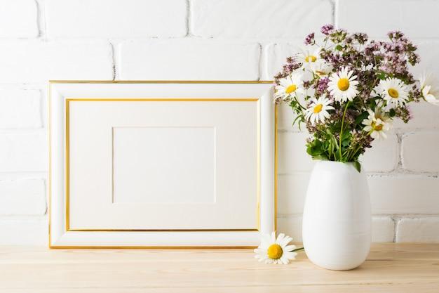 Mockup di cornice paesaggio decorato oro con bouquet di fiori selvatici in fiore
