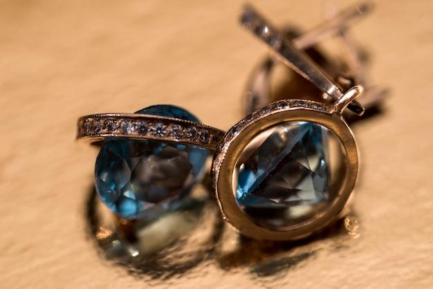 Orecchini in oro con cristalli sullo sfondo