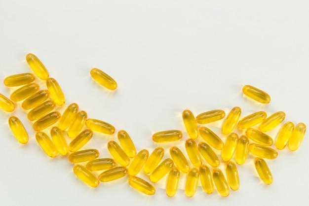 Capsule dell'olio di pesce dell'oro su priorità bassa bianca con lo spazio della copia. tema salute e farmacia