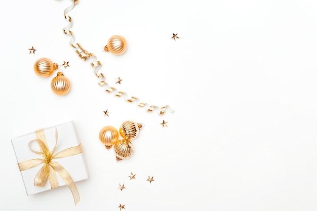 Piatto d'oro con scatola regalo e palle di natale dorate decorative sfondo bianco spazio copia