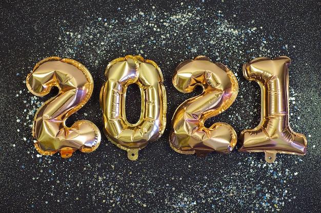 Palloncini in lamina d'oro a forma di numeri 2021 su fondo nero