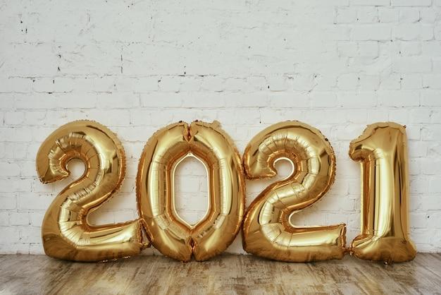 Palloncini in lamina d'oro a forma di numeri 2021 sul muro di mattoni bianchi
