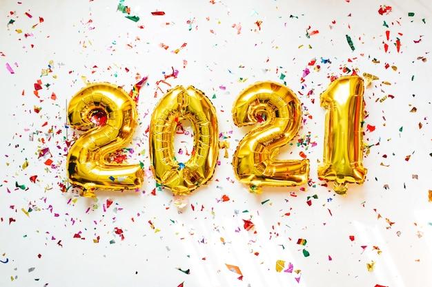 Palloncini in lamina d'oro numero 2021 con coriandoli colorati su sfondo bianco. felice anno nuovo 2021 celebrazione.