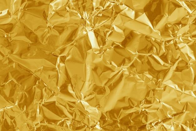 Struttura lucida foglia di lamina d'oro, carta da imballaggio gialla per lo sfondo.