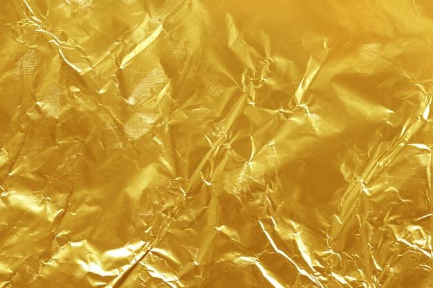 Texture lucida foglia oro foglia, carta da imballaggio gialla per lo sfondo.
