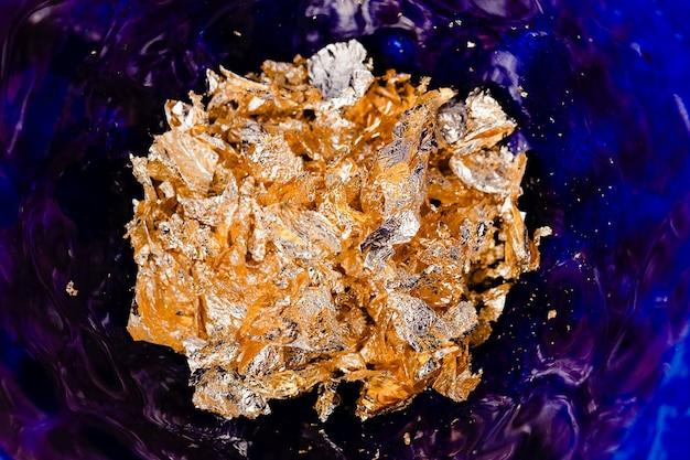 Scaglie di metallo lamina d'oro su fondo smaltato blu intenso