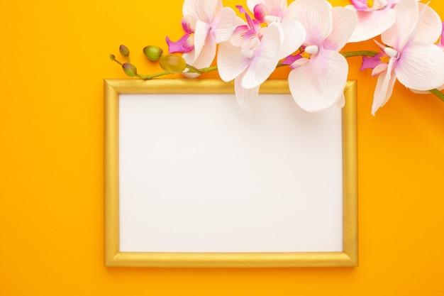 Cornice dorata su sfondo giallo con orchidea con posto per il testo. foto di alta qualità