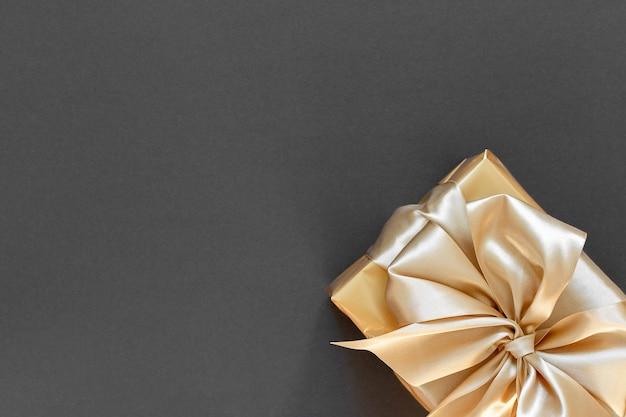 Regalo d'oro, scatola con nastro d'oro e fiocco su nero, piatto laici