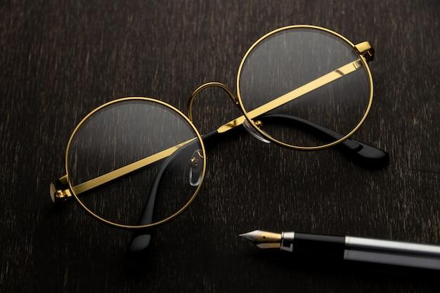 Occhiali d'oro, penna su uno sfondo di legno scuro..