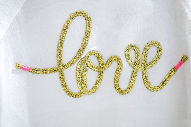 Il testo artigianale d'oro love typo knitting sul tessuto bianco.