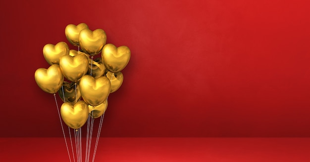 Mazzo di palloncini a forma di cuore d'oro su una superficie rossa