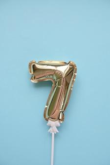 Gonfiabile numero 7 in oro su un bastone su sfondo blu. concetto di vacanza, compleanno, anniversario.
