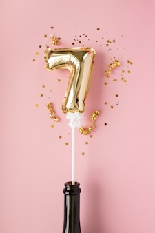 Gonfiabile numero 7 in oro su un bastone in una bottiglia di champagne circondato da paillettes su uno sfondo rosa.