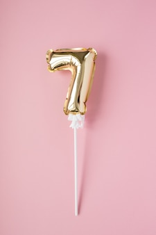 Gonfiabile numero 7 in oro su un bastone su sfondo rosa. concetto di vacanza, compleanno, anniversario.