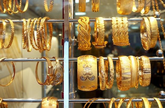 I braccialetti di gioielli d'oro sono appesi a un supporto