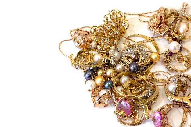 Rottami di gioielli in oro su sfondo bianco, concetto di banco dei pegni, ispezione e verifica dei gioielli