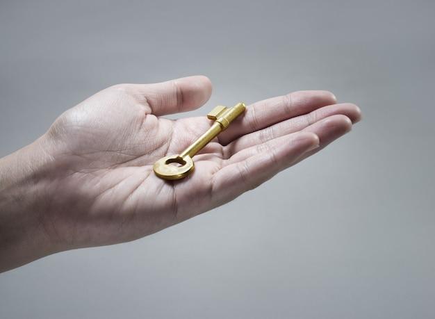Chiave d'oro sulla mano umana. concetto di business