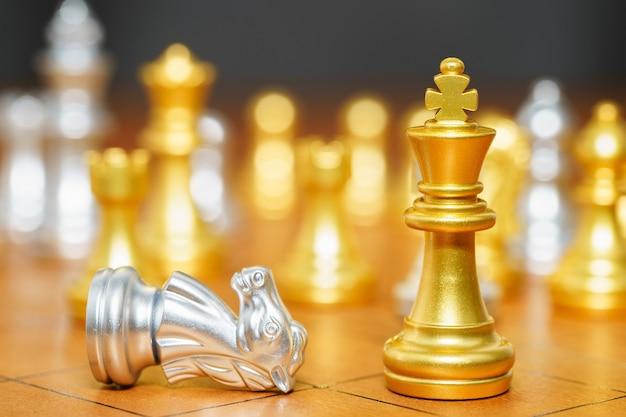 Pezzo degli scacchi re d'oro e pezzi degli scacchi del cavallo stanno sulla scacchiera in legno, concetto di gioco di strategia di leadership