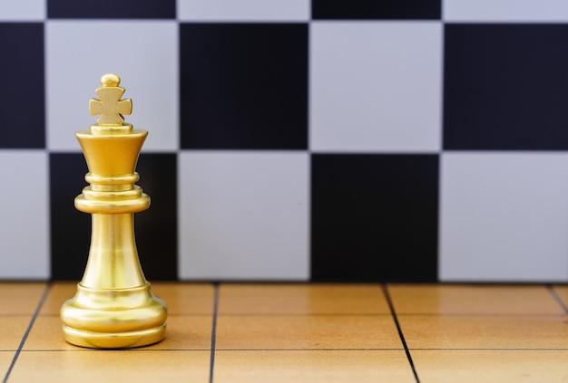 Il pezzo degli scacchi re d'oro si trova sulla scacchiera in legno, concetto di gioco di strategia di leadership