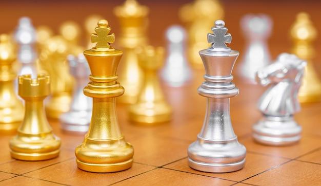 Pezzo degli scacchi re d'oro e vari pezzi degli scacchi stanno sulla scacchiera in legno, concetto di gioco di strategia di leadership