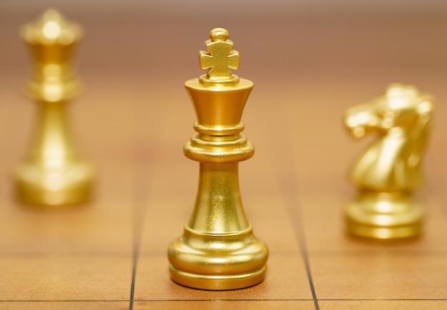 Il pezzo degli scacchi del re d'oro e vari pezzi degli scacchi stanno sulla scacchiera in legno