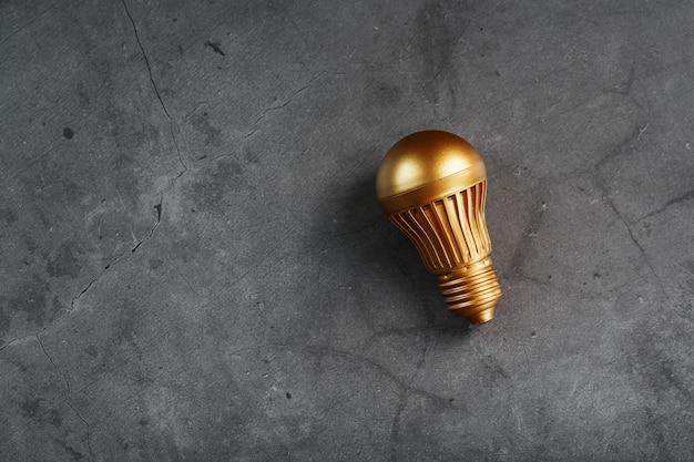 Lampadina dell'oro su una superficie strutturata nera