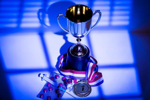 Medaglia d'oro e coppa del campione, siringa con sostanza dopante, compressa di pillole e fiala con sostanza vietata con luci e ombre di una tenda che entra dalla finestra di notte. concetto di doping