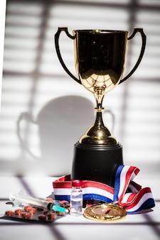 Medaglia d'oro e coppa del campione, siringa con sostanza dopante, pastiglia e fiala con sostanza vietata con luci e ombre di una tenda che entra dalla finestra. sport e concetto di doping