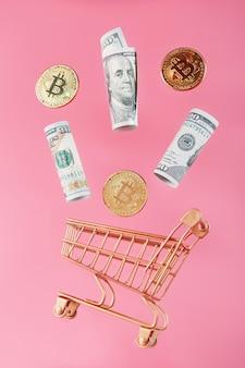 Mini carrello d'oro con monete bitcoin e dollari usa in un volo di levitazione su una superficie rosa