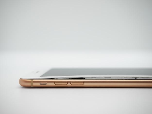 Separazione del display dello smartphone moderno color oro dalla custodia a causa della batteria gonfia