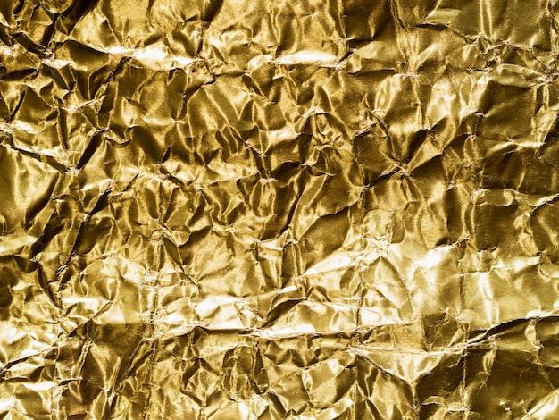 Oro dipinto in un foglio giallo stropicciato