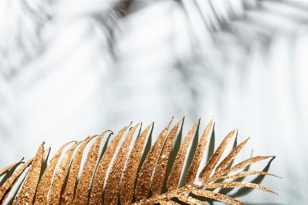 Foglie di palma d'oro e ombre su una parete blu.