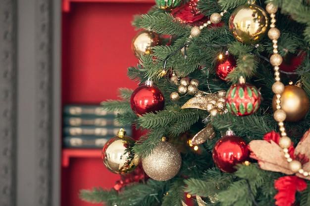 Oro e giocattoli di natale rossi, palline, ghirlande su un ramo di abete rosso su sfondo rosso scuro.