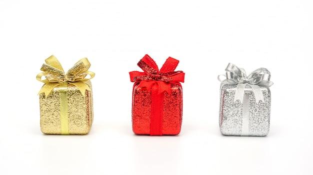Confezione regalo oro, rosso e argento su sfondo bianco.