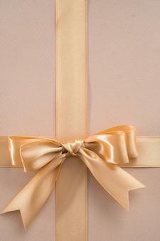 Nastro d'oro con fiocco su sfondo dorato