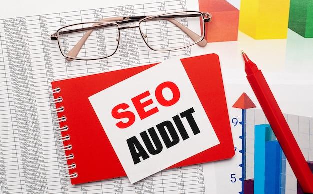 Occhiali cerchiati d'oro, una penna rossa, tabelle dei colori e un taccuino rosso con una scheda bianca con il testo audit seo sul desktop