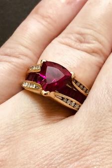 Anello in oro con rubino e diamanti sulle mani delle donne