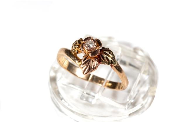 Anello in oro con un piccolo diamante. cornice a forma di foglie di vite a base di black hills