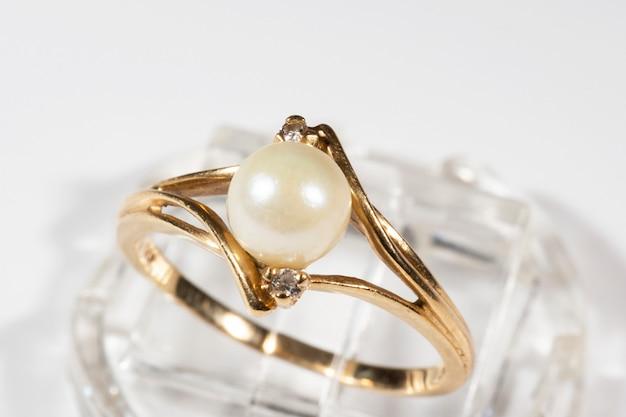Un anello in oro con una perla tonda bianca e due piccoli diamanti, una decorazione sofisticata