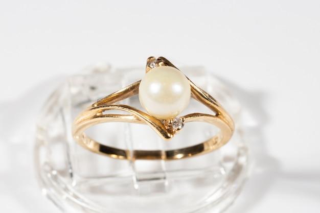 Un anello in oro con una perla tonda bianca e due piccoli diamanti