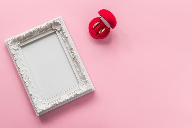 Anelli d'oro in scatola rossa e cornice per foto con spazio vuoto sul rosa